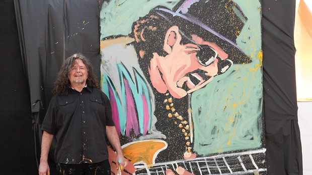 Gregory Adamson next to finished Carlos Santana painting